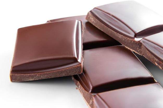 Foto macro de barras de chocolate ao leite em um branco. pedaços quebrados colocados na pilha, isolados em um plano de fundo.