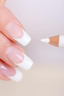 Foto macro de dedos femininos com um lápis branco de manicure