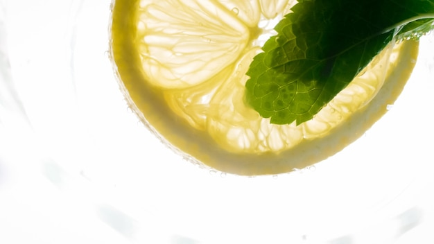 Foto macro de fatia de limão e folha de hortelã flutuando na limonada gelada.