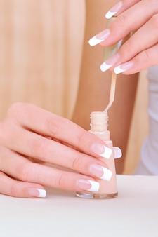 Foto macro de mãos femininas com esmalte de garrafa