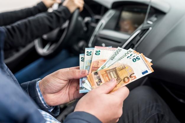 Foto macro de mãos masculinas segurando notas de euro