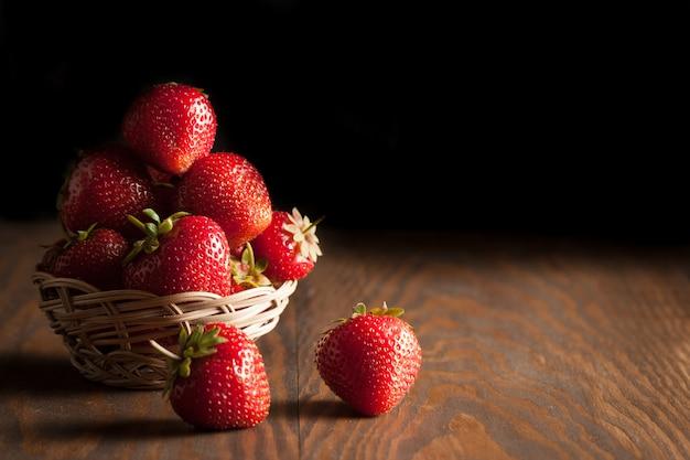 Foto macro de morango vermelho maduro fresco em uma tigela de madeira com fundo rústico. produtos naturais orgânicos.