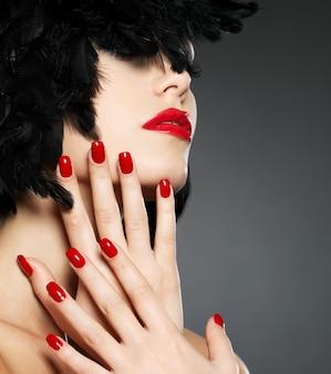Foto macro de mulher com unhas vermelhas e lábios sensuais.