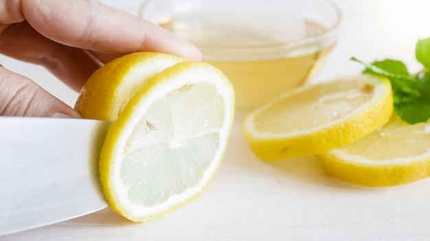 Foto macro de pessoa cortando limão maduro com faca.