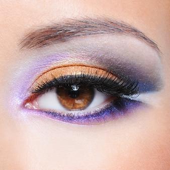 Foto macro de um olho feminino com maquiagem saturada de moda