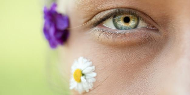 Foto macro do belo olho de uma mulher e flores silvestres no rosto