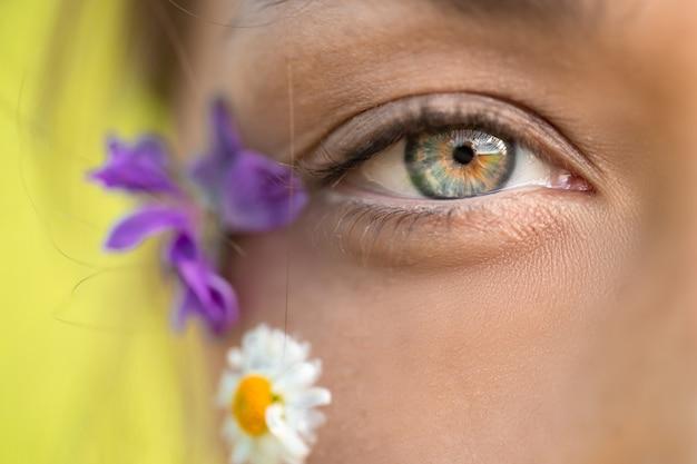Foto macro do lindo olho de uma mulher e flores silvestres
