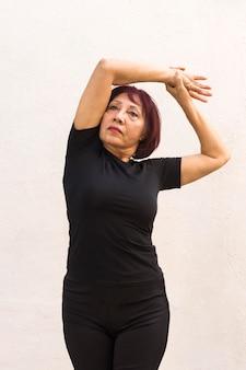 Foto média da mulher fazendo exercícios de aquecimento