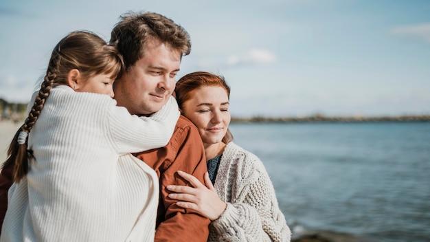 Foto média de família feliz à beira-mar