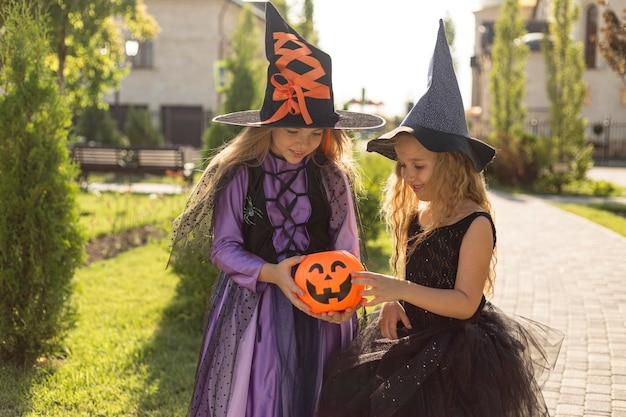 Foto média de meninas com saco de doces de abóbora