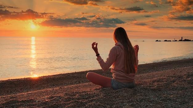 Foto média de mulher meditando sobre o mar antes do pôr do sol, silêncio e conceito de relaxamento