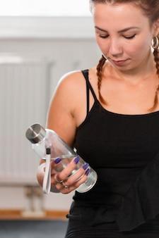 Foto média de mulher segurando uma garrafa de água