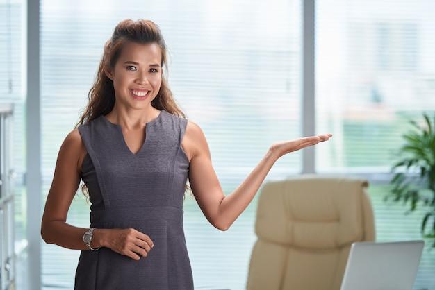 Foto média do modelo asiático, gesticulando como se estivesse apresentando um produto em um comercial