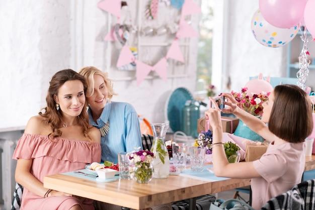 Foto memorável. mulher de cabelos escuros tirando fotos memoráveis de seus amigos enquanto celebra o chá de bebê