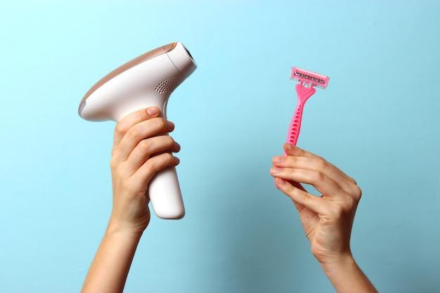 Foto moderna em casa de depiladora e lâmina de barbear em mãos femininas - remoção de pelos sem tratamento