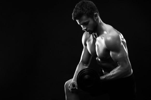 Foto monocromática de um jovem atleta atlético com halteres