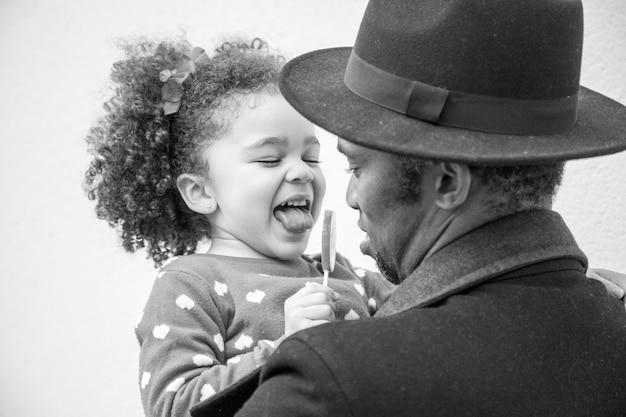 Foto monocromática de uma filha e um pai juntos