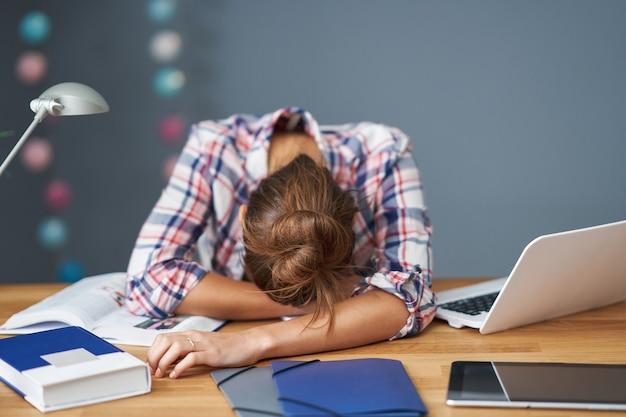 Foto mostrando aluna cansada aprendendo tarde em casa