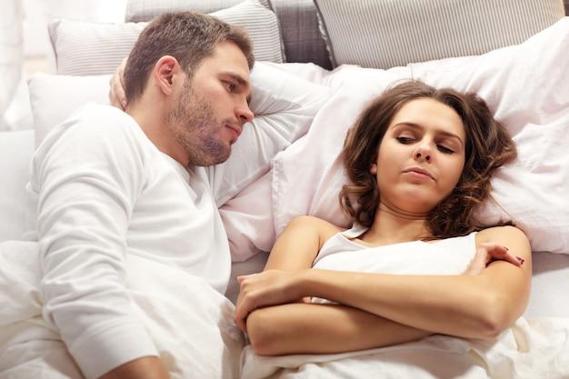 Foto mostrando casal infeliz discutindo na cama