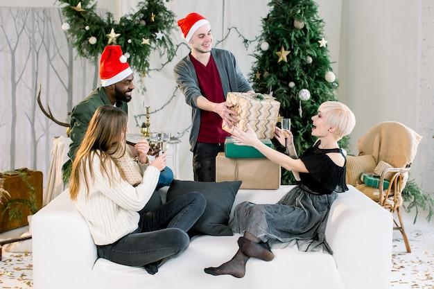 Foto mostrando um grupo de amigos comemorando o natal e apresentando presentes