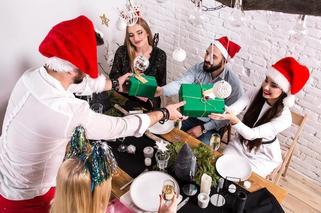 Foto mostrando um grupo de amigos comemorando o natal em casa e dando presentes uns aos outros