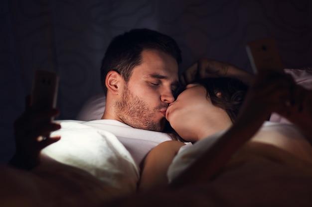 Foto mostrando um jovem casal usando smartphones na cama à noite
