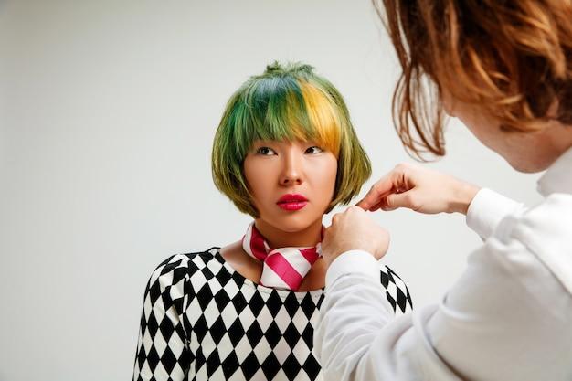 Foto mostrando uma mulher adulta no salão de cabeleireiro. foto de estúdio de graciosa jovem com corte de cabelo curto elegante e cabelo colorido em fundo cinza e mãos de cabeleireiro.
