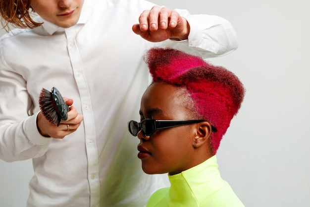Foto mostrando uma mulher afro-americana no cabeleireiro. foto de estúdio de graciosa jovem com corte de cabelo curto elegante e cabelo colorido em fundo cinza e mãos de cabeleireiro.