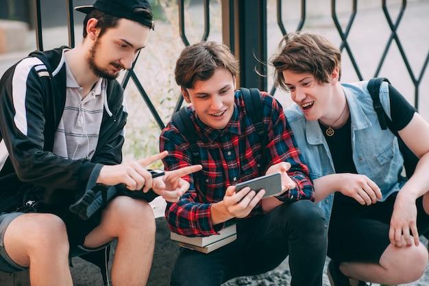 Foto móvel criativa. tecnologia moderna. os alunos saem depois das aulas. estilo de vida moderno da juventude. melhor conceito de comunicação de amizade