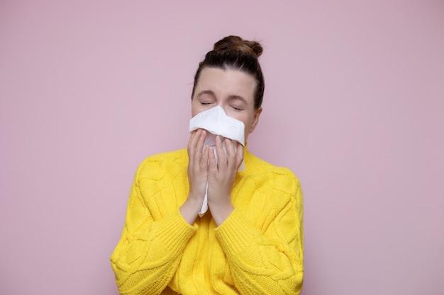 Foto mulher doente com suéter espirra no guardanapo no fundo rosa, rinite alérgica.