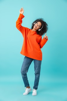 Foto multicolorida de comprimento total de mulher satisfeita em jeans casuais dançando enquanto ouve música usando fones de ouvido sem fio, isolados sobre a parede azul