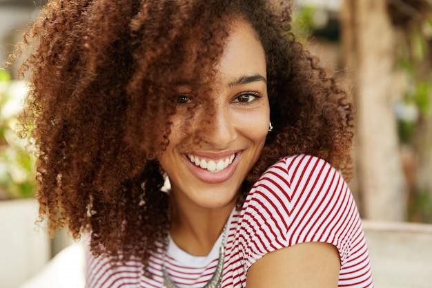 Foto na cabeça de adorável linda mulher com cabelos cacheados e sorriso agradável, usa camiseta listrada, tem dentes brancos e uniformes, fica de bom humor após namorar. pessoas, etnia e positividade