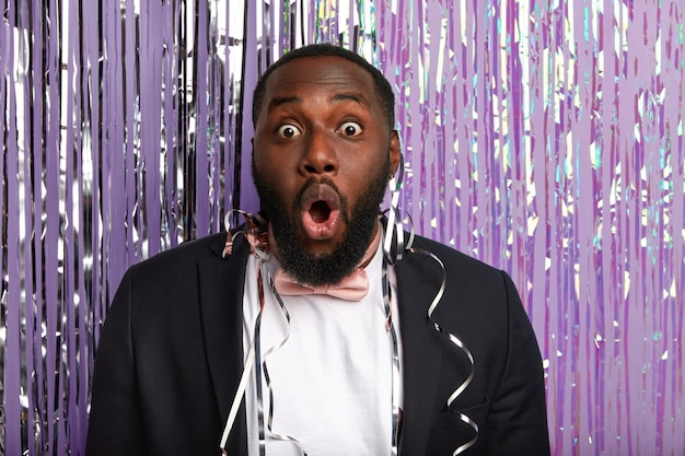 Foto na cabeça de um afro-americano barbudo com expressão atordoada, mantém a boca aberta, maravilhado com música alta, entra na festa, usa terno formal com gravata borboleta rosa, diz omg, aproveita a vida noturna