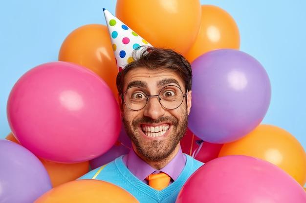 Foto na cabeça de um cara bonito e alegre cercado por balões de festa posando