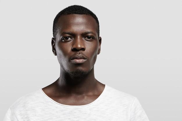 Foto na cabeça de um estudante africano sério e atraente com barba e bigode pequenos, vestido com uma camiseta casual com expressão confiante e pensativa no rosto em pé na parede cinza