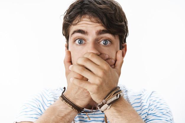 Foto na cabeça de um homem jovem e bonito surpreso e atordoado com olhos azuis cobrindo a boca, sentindo-se muito animado e chocado levantando as sobrancelhas em espanto ao ouvir novos rumores espalhados pelo escritório
