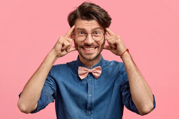 Foto na cabeça de um homem satisfeito mantém as mãos nas têmporas, sorri amplamente, tem um penteado moderno, vestido com roupas estilosas, pensa em algo agradável