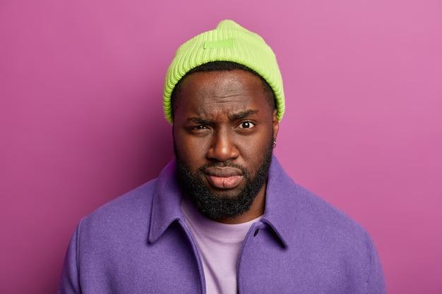 Foto na cabeça de um homem sério e atraente com pele escura, lábios carnudos, olha misteriosamente para a câmera, usa chapéu verde e casaco roxo, fica dentro de casa