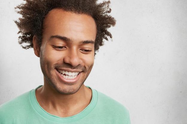 Foto na cabeça de um homem tímido de pele escura com cabelo crespo, sorri amplamente, mostra os dentes brancos e uniformes,