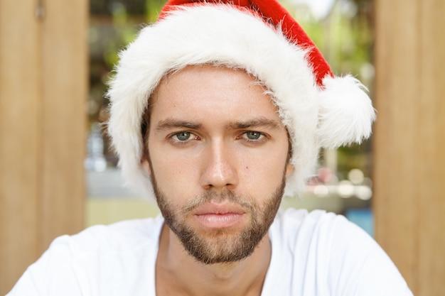 Foto na cabeça de um jovem atraente com a barba por fazer usando um chapéu de papai noel e parecendo infeliz