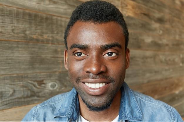Foto na cabeça de um jovem e atraente estudante barbudo de pele escura em uma camisa jeans elegante, sorrindo alegremente, mostrando seus dentes brancos perfeitos, olhando de lado com um sorriso inspirado e feliz horizontal
