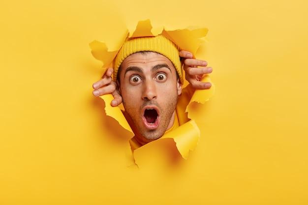 Foto na cabeça de um jovem estupefato com aparência europeia, usando chapéu amarelo