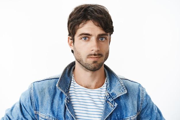 Foto na cabeça de um jovem hispânico atraente com olhos azuis e barba em uma jaqueta jeans sobre uma camiseta listrada, olhando para frente com uma expressão simpática e simpática, sorrindo enquanto aprecia a vista do novo apartamento