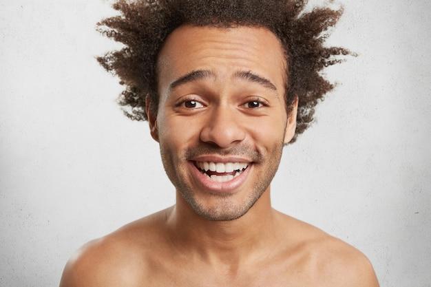 Foto na cabeça de um rapaz de aparência agradável com cabelo desgrenhado, cerdas, sorrisos felizes,