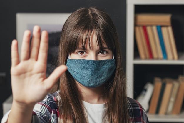 Foto na cabeça de uma adolescente com uma máscara protetora feita à mão, mostrando a palma da mão com a placa de pare