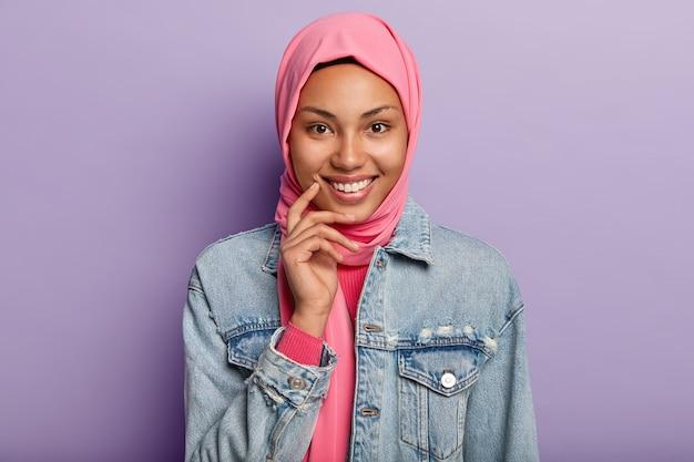 Foto na cabeça de uma adorável mulher árabe de pele escura mantém a mão suavemente perto do rosto, sorri amplamente e olha diretamente para a câmera