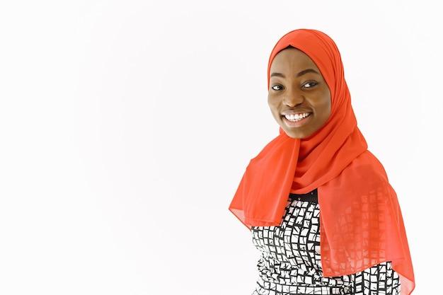 Foto na cabeça de uma adorável mulher muçulmana religiosa satisfeita com um sorriso gentil, pele escura e saudável, usa um lenço na cabeça. isolado sobre fundo branco.