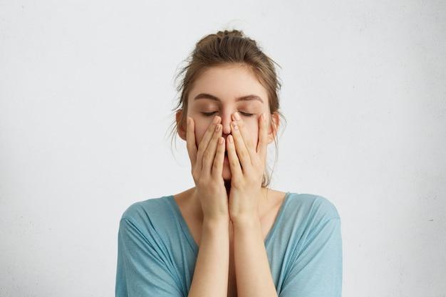 Foto na cabeça de uma bela jovem fechando os olhos de mãos dadas no queixo, cansada