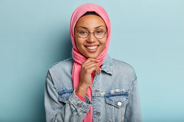 Foto na cabeça de uma bela mulher árabe com sorriso cheio de dentes, segura o queixo, usa óculos redondos e usa roupas tradicionais especiais