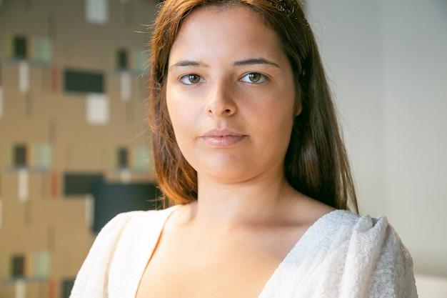 Foto na cabeça de uma jovem bonita e confiante olhando para a câmera e posando dentro de casa